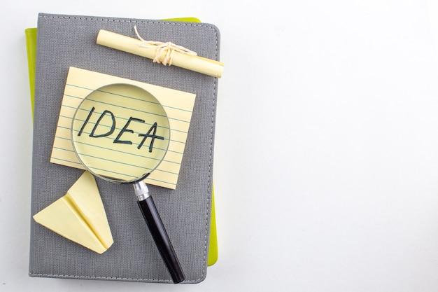 Bovenaanzicht idee geschreven op kleverige nota lupa op blocnotes op witte tafel vrije ruimte