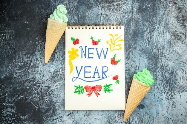 Bovenaanzicht ijsjes nieuwjaar geschreven op notebook op grijze achtergrond