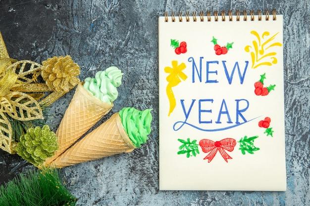 Bovenaanzicht ijsjes xmas ornamenten nieuwjaar geschreven op laptop op grijze achtergrond