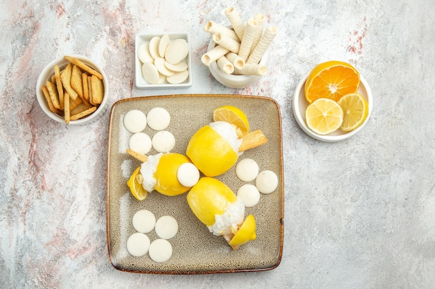 Bovenaanzicht ijskoude citroenen met snoepjes en crackers op witte tafel