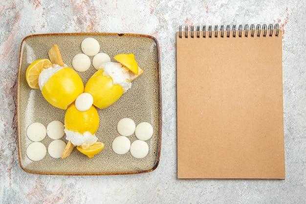 Bovenaanzicht ijskoude citroenen met witte snoepjes op de witte tafel