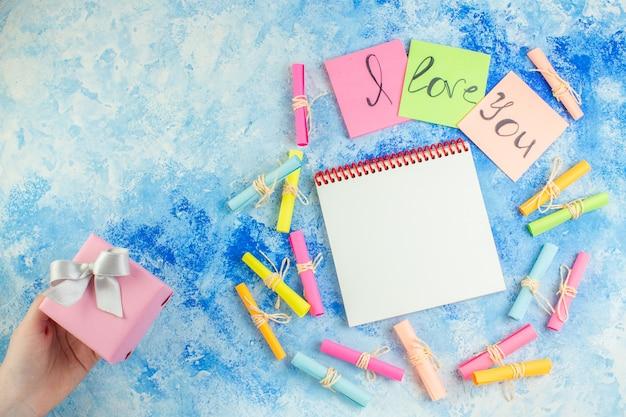Bovenaanzicht ik hou van je geschreven op plaknotities scroll wenspapieren cadeau in menselijke hand notitieblok op blauwe achtergrond