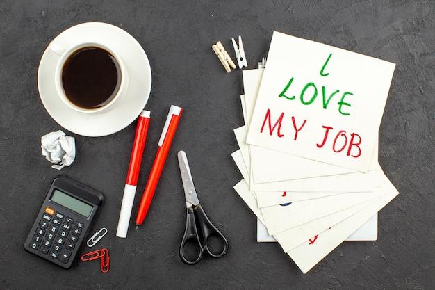 Bovenaanzicht ik hou van mijn baan geschreven op notitiepapier wasknijpers schaar rekenmachine kopje thee rode pen en marker op zwart