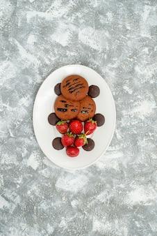Bovenaanzicht in de verte chocoladekoekjes, aardbeien en ronde chocolaatjes op het witte ovale bord op de grijswitte ondergrond