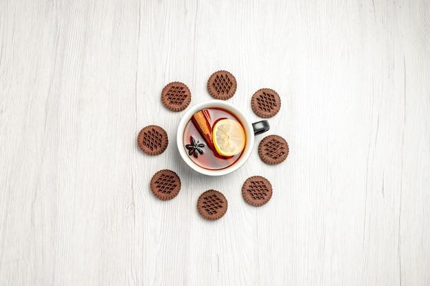 Bovenaanzicht in de verte citroen-kaneelthee afgerond met koekjes op de witte houten tafel