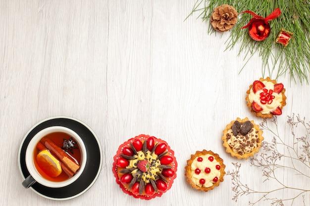 Bovenaanzicht in de verte een kopje citroen-kaneel-thee-bessencake-taartjes onderaan en de pijnboombladeren met kerstspeelgoed rechtsboven op de witte houten grond