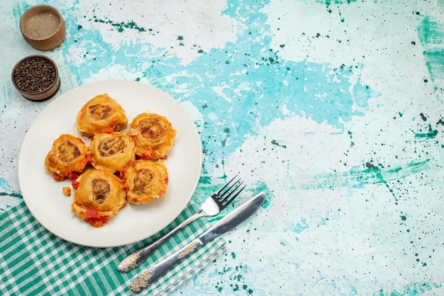 Bovenaanzicht in de verte gekookte deegmaaltijd met gehakt in plaat met paprika op helder bureau, caloriekleur van het voedsel van de deegmaaltijd