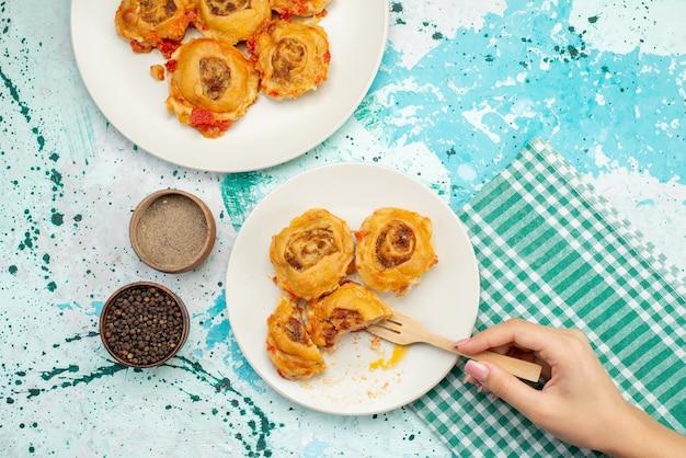 Bovenaanzicht in de verte gekookte deegmaaltijd met gehakt in platen op helderblauw bureau, caloriekleur van het deegvoedsel