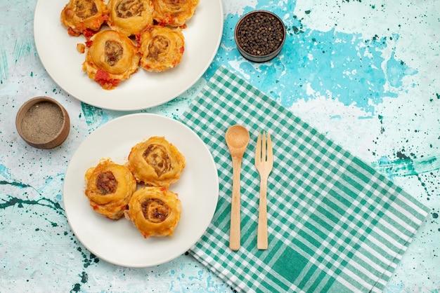 Bovenaanzicht in de verte gekookte deegmaaltijd met gehakt in platen op helderblauw