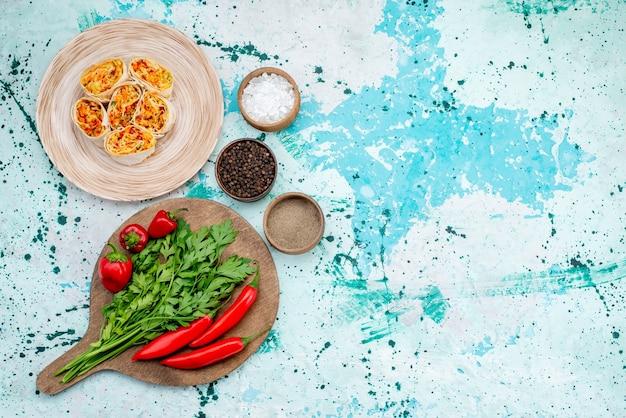 Bovenaanzicht in de verte gesneden groente rolt deeg met smakelijke vulling samen met greens en rode pittige paprika's op helderblauw bureau, voedselrol groente