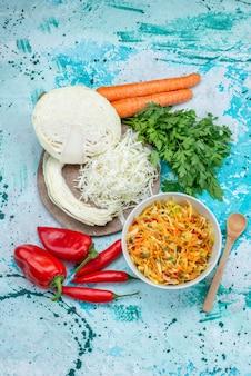 Bovenaanzicht in de verte gesneden verse groenten lange en dunne stukjes salade binnen plaat met groene kool paprika's op helderblauwe, voedsel maaltijd groentesalade
