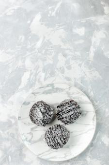 Bovenaanzicht in de verte heerlijke chocoladeballen rond gevormde taarten met suikerglazuur op lichtwit bureau bak cake chocolade suikertaart zoet