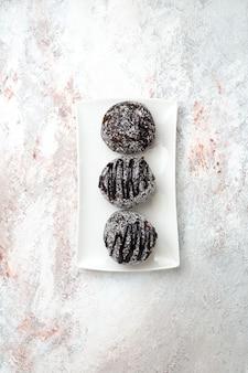 Bovenaanzicht in de verte heerlijke chocoladetaarten met suikerglazuur op witte ondergrond chocolade suiker koekje zoete cake bak koekje