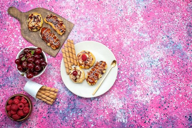 Bovenaanzicht in de verte heerlijke fruitige cakes met room en chocolade in een witte plaat samen met vers fruit op het heldere bureau.
