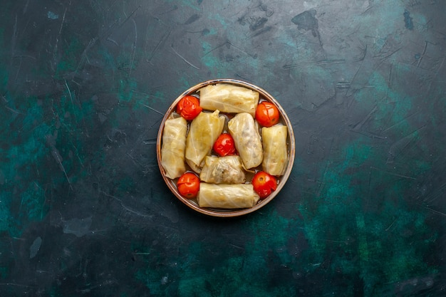 Bovenaanzicht in de verte heerlijke vleesmaaltijd gerold in kool met tomaten op donkerblauw bureau