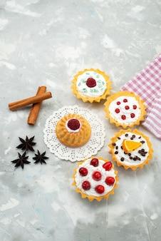 Bovenaanzicht in de verte kleine d cakes met roomkaneel en verschillende vruchten geïsoleerd op het lichte zoete oppervlak