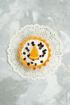 Bovenaanzicht in de verte kleine heerlijke cake met room en gedroogd fruit op het lichte oppervlak van zoete deegsuiker
