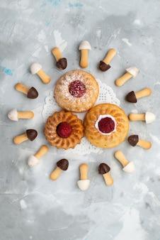Bovenaanzicht in de verte kleine heerlijke cakes met chocoladekoekjes op het grijze oppervlak