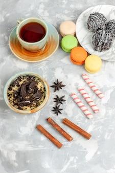 Bovenaanzicht in de verte kopje thee met macarons dessert en chocoladetaart op wit bureau bak cake biscuit suiker zoete taart