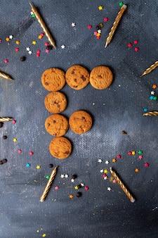 Bovenaanzicht in de verte lekkere chocoladekoekjes met kaarsen en decoraties op de donkergrijze achtergrond cookie biscuit zoete thee suiker