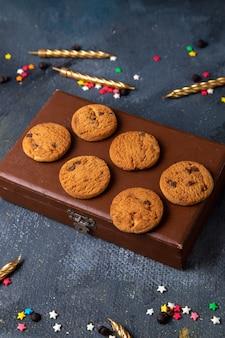 Bovenaanzicht in de verte lekkere chocoladekoekjes op het bruine doosje met gekleurde sterretjes en kaarsen op de donkergrijze achtergrond koekjeskoekje zoete thee