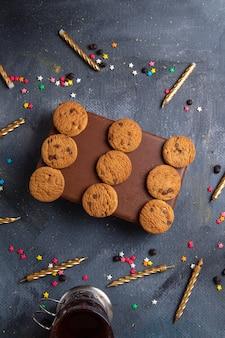 Bovenaanzicht in de verte lekkere chocoladekoekjes op het bruine doosje met theekaarsen op de donkergrijze achtergrond koekjeskoekje zoete thee