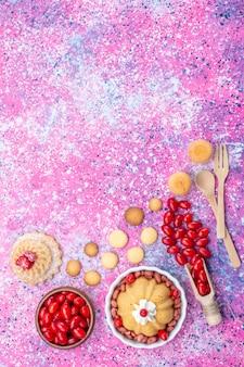 Bovenaanzicht in de verte lekkere gewone cake met room en verse pinda's rode kornoeljes op helder licht bureau, cakekoekje zoete notenbes