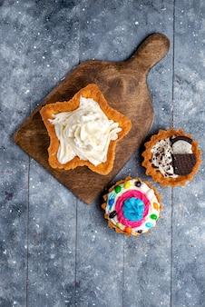 Bovenaanzicht in de verte lekkere romige taarten in de vorm van een ster met koektaarten op lichte, cake, koekjesroom, zoete thee