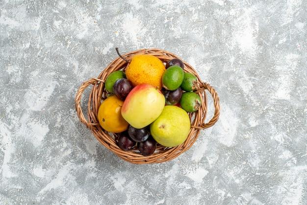 Bovenaanzicht in de verte plastic rieten mand met appelperen, feykhoas-pruimen en persimmon in het midden van de grijze tafel