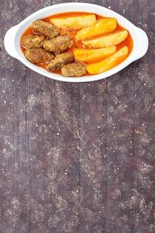 Bovenaanzicht in de verte smakelijke vleeskoteletten gekookt samen met aardappelen en saus in plaat op bruin, vlees aardappel gerecht maaltijd diner