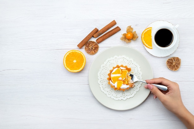 Bovenaanzicht in de verte van kleine cake met room en gesneden sinaasappels samen met koffie en kaneel op licht bureau, fruitcake biscuit zoete suiker