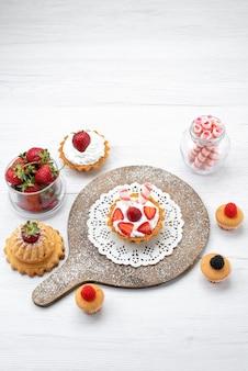 Bovenaanzicht in de verte van kleine heerlijke cake met room en gesneden aardbeientaarten op wit bureau, cake bessen zoet bakken fruit bakken
