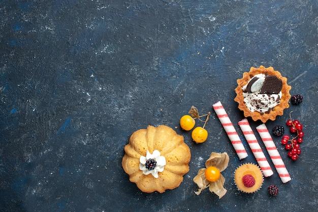 Bovenaanzicht in de verte van kleine heerlijke cake samen met koekje en roze stoksuikergoedvruchten op donker bureau, koektaartfruit