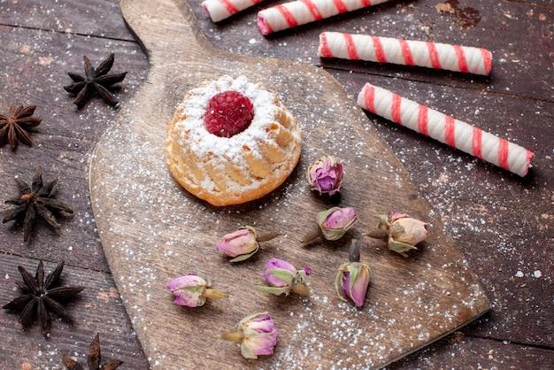 Bovenaanzicht in de verte van kleine romige cake met framboos samen met roze stoksnoepjes op bruin houten, snoep zoete suiker bakcake