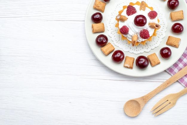 Bovenaanzicht in de verte van kleine romige cake met frambozen en kleine koekjes op wit-licht bureau, fruitcake zoete bessenroom