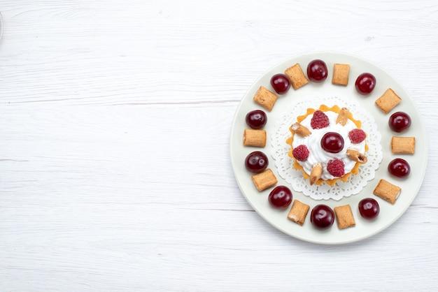 Bovenaanzicht in de verte van kleine romige cake met frambozen en kleine koekjes op wit-licht, fruitcake zoete bessenroom kers