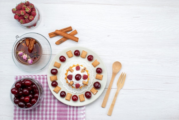 Bovenaanzicht in de verte van kleine romige cake met frambozen, kersen en kleine koekjes, thee kaneel op wit bureau, fruitcake, bessenroom suiker thee