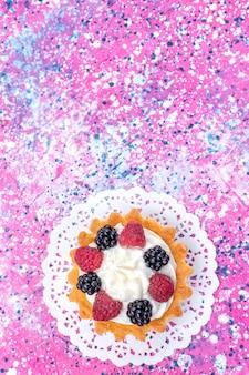 Bovenaanzicht in de verte van kleine romige cake met verschillende bessen op licht helder, cake biscuit bessen zoet bakken