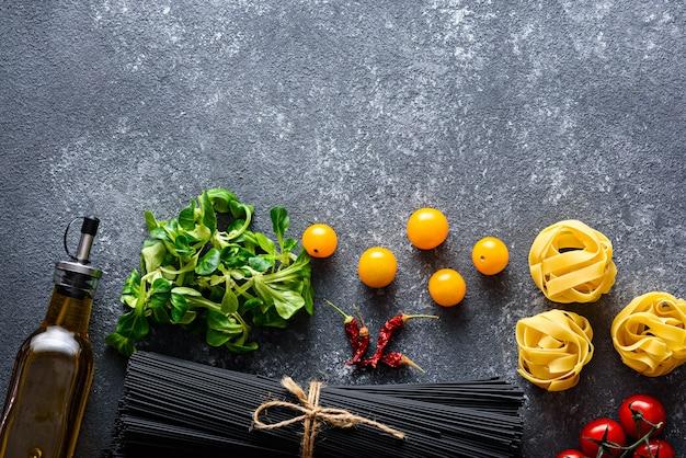 Bovenaanzicht ingrediënten van zwarte spaghetti uit de italiaanse keuken met inktvis inkt, fettuccine, tomaten, sla, chilipeper, fles olijfolie op zwarte achtergrond met kopie ruimte