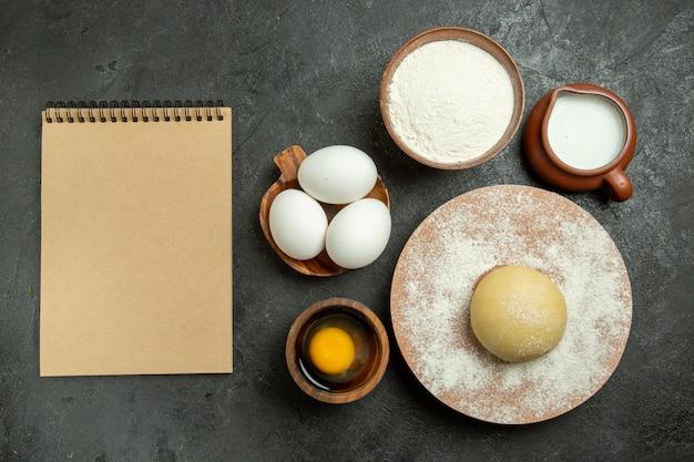 Bovenaanzicht ingrediënten voor deeg melkeieren meel op de grijze ruimte