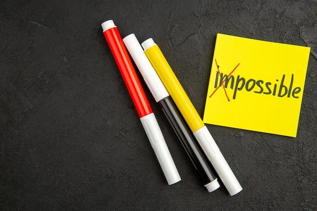 Bovenaanzicht inspirerende notitie met potloden op donkere ondergrond kleur schrijfboek pen schrijven notitieblok foto