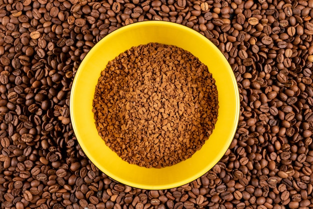 Bovenaanzicht instant koffie in gele plaat op koffiebonen oppervlak