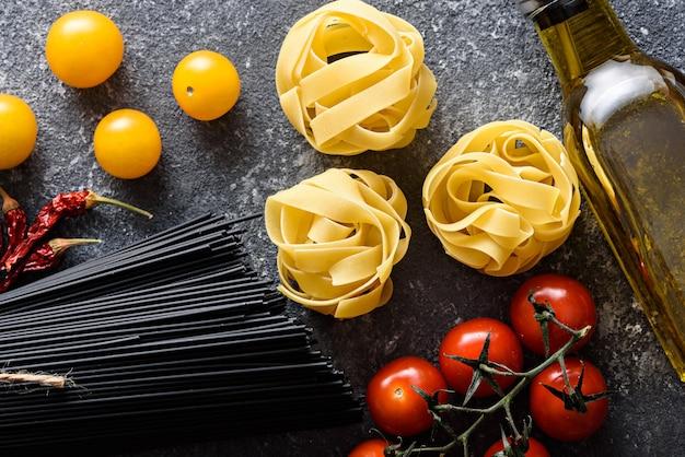 Bovenaanzicht italiaans diner van pasta, zwarte spaghetti, fettuccine, tomaten, olijfolie op grijze achtergrond, kookconcept