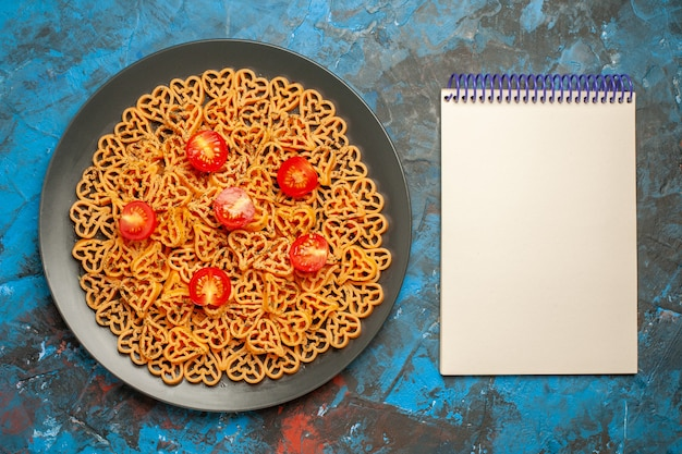 Bovenaanzicht italiaanse pasta harten gesneden cherrytomaatjes op zwarte ovale plaat notitieblok op blauwe tafel