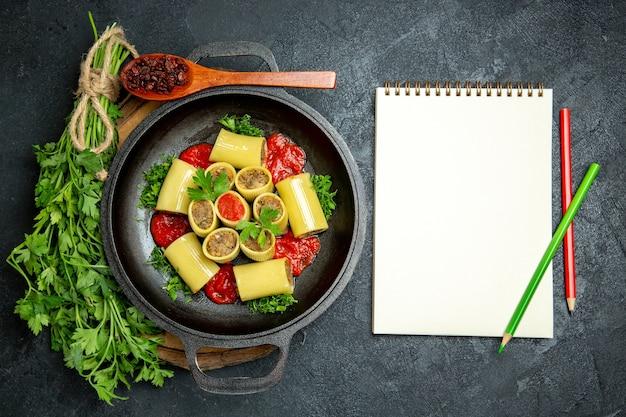 Bovenaanzicht italiaanse pasta met groene tomatensaus en vlees in pan op donkergrijze ruimte