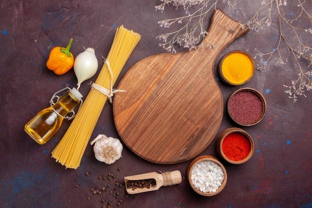 Bovenaanzicht italiaanse pasta met kruiden op donkere ruimte