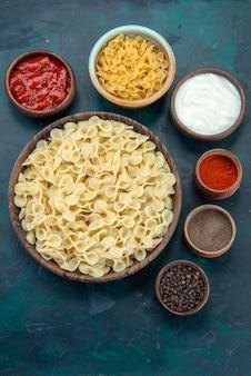 Bovenaanzicht italiaanse pasta met verschillende kruiden in het donker