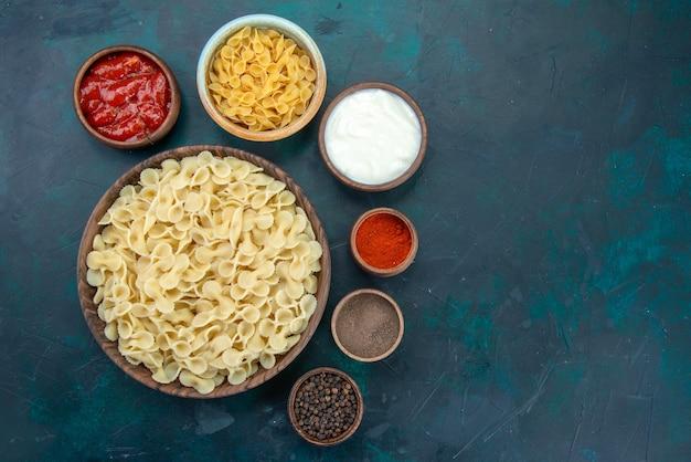Bovenaanzicht italiaanse pasta met verschillende kruiden op blauw