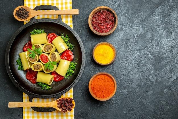 Bovenaanzicht italiaanse pasta met vlees en kruiden op grijze ruimte