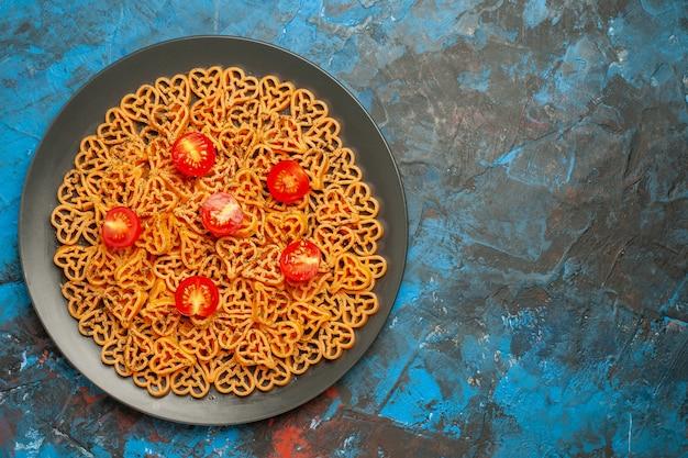 Bovenaanzicht italiaanse pastaharten gesneden kerstomaatjes op zwarte ovale plaat op blauwe tafel met kopieerplaats